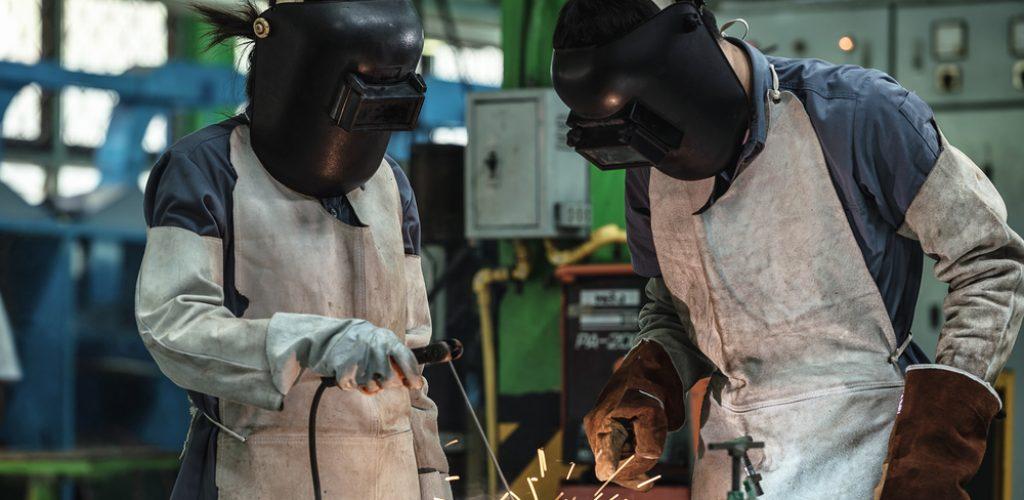 Två industriarbetare svetsar